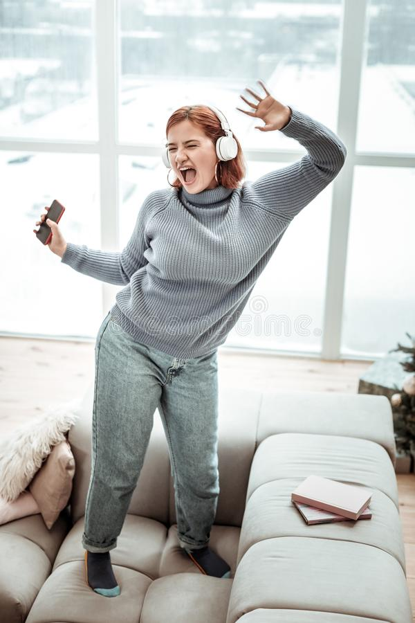 Young red-haired beaming girl in a grey sweater feeling happy royalty free stock image