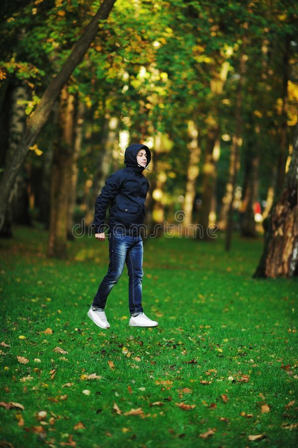 A wonderful picture with depth and volume, creating a deceptive. Effect that a young serious man in a jacket with a hood, as if, goes high above the grass in stock images