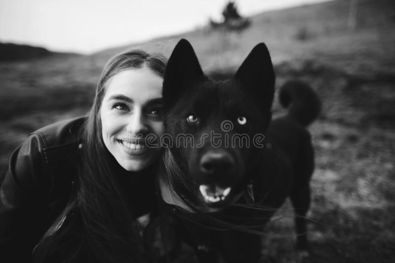 A wonderful portrait of a girl and her dog with colorful eyes. Black and white photo. A wonderful portrait of a girl and her dog with colorful eyes. Friends are stock photos