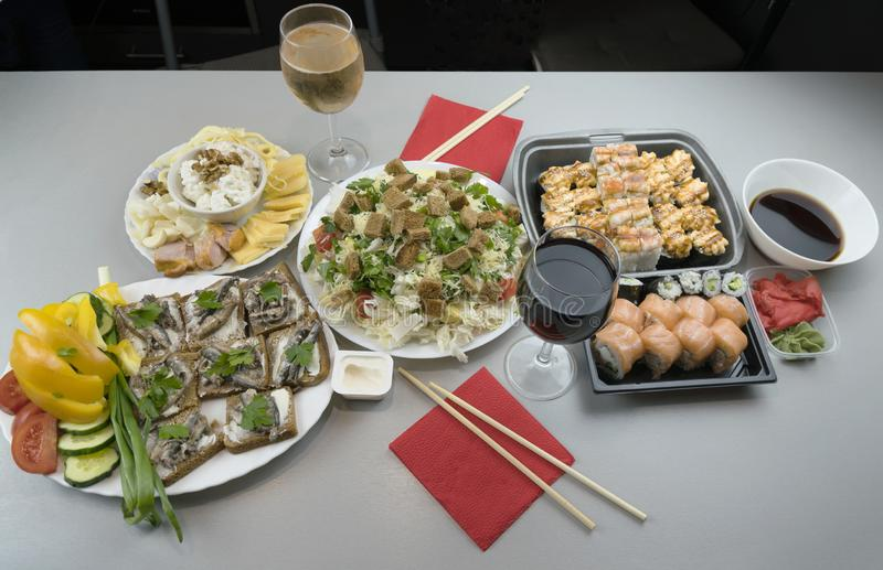 A wonderful romantic dinner for two with Japanese rolls and glasses of red wine and white wine royalty free stock photography