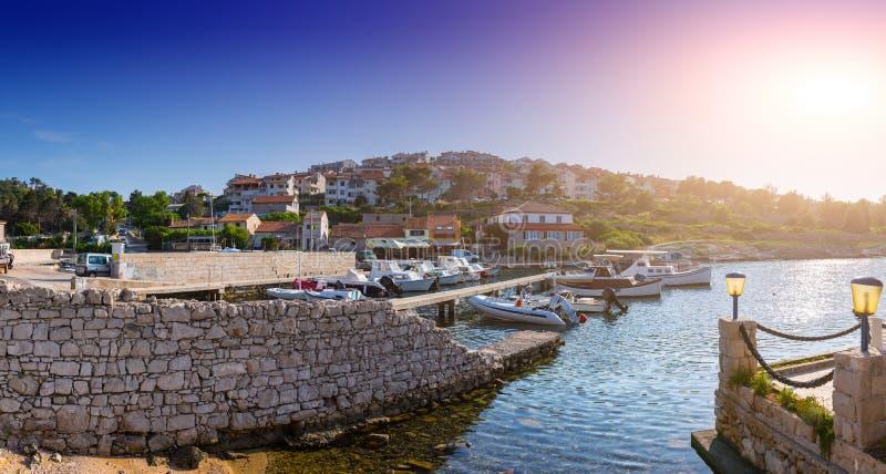 Wonderful romantic summer evening landscape marine in backlit sunset sunbeam panorama at coastline Adriatic sea. Fishing boats royalty free stock photos