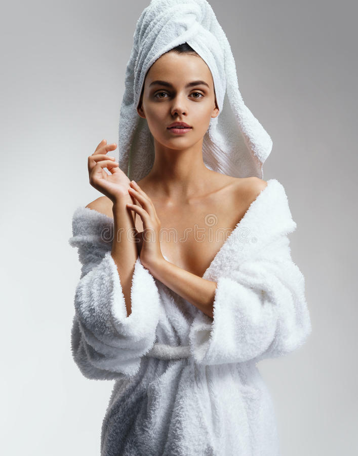 Wonderful slim girl in white bathrobe after spa. royalty free stock photos