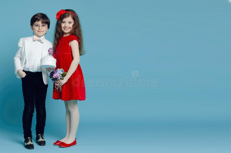 A wonderful boy and girl with smile standing together and posing in casual clothes, isolated on turquoise background. stock photos