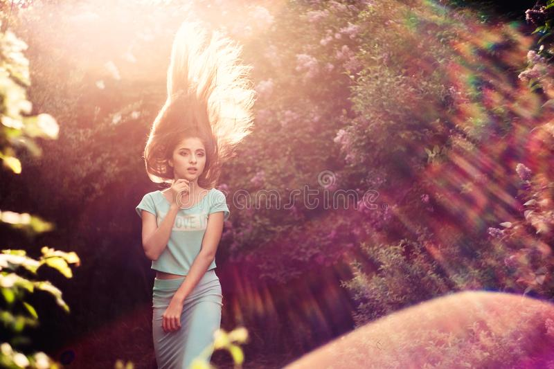 Wonderful spring. A beautiful young girl enjoys nature and sunlight among the blossoming lilac. stock image