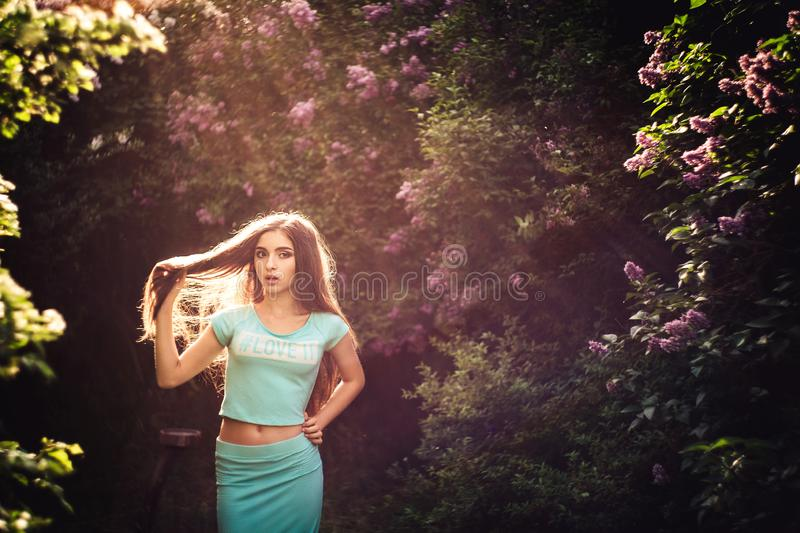 Wonderful spring. A beautiful young girl enjoys nature and sunlight among the blossoming lilac. royalty free stock images