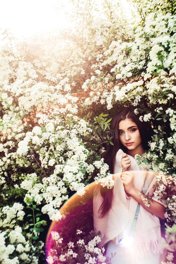 Wonderful spring. Beautiful young girl enjoys nature and sunlight among the blossoming spirea. stock photos