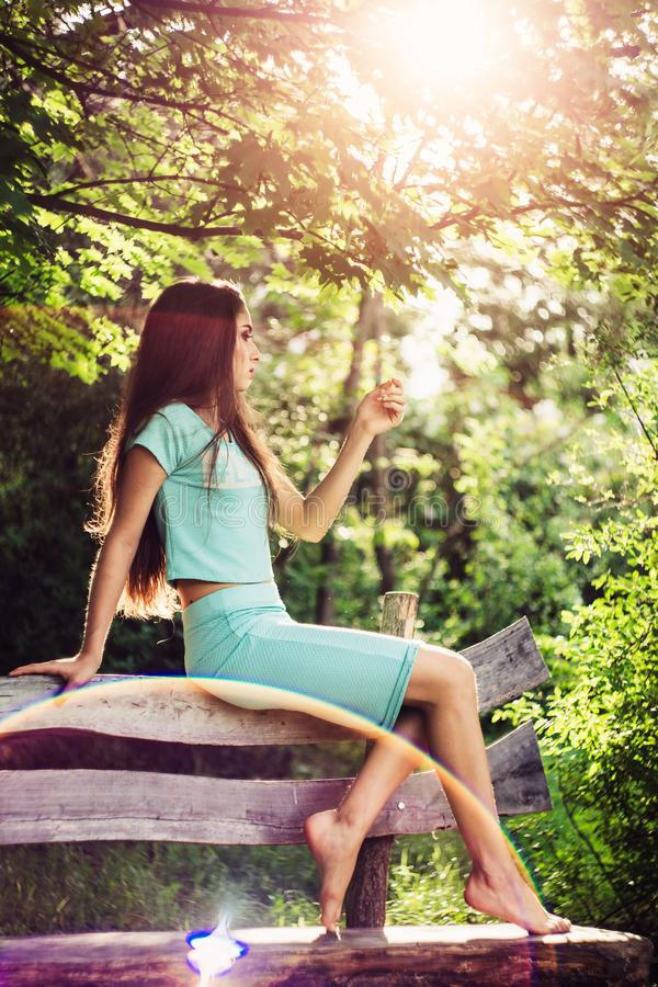 Wonderful spring. Beautiful young girl enjoys nature and sunlight sitting on a wooden bench in the park. stock images
