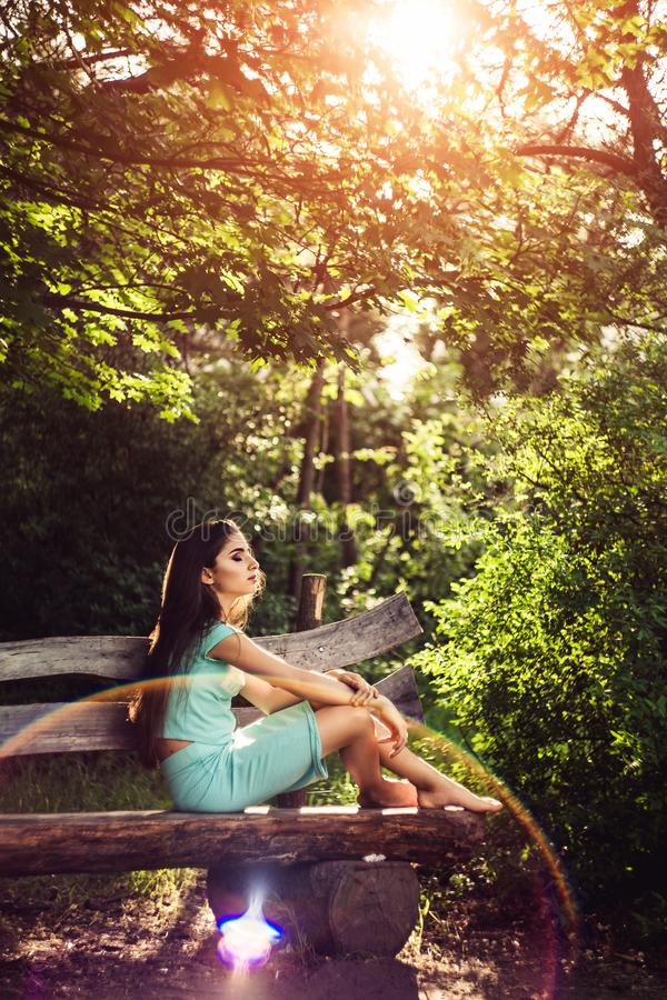 Wonderful spring. Beautiful young girl enjoys nature and sunlight sitting on a wooden bench in the park. royalty free stock photos