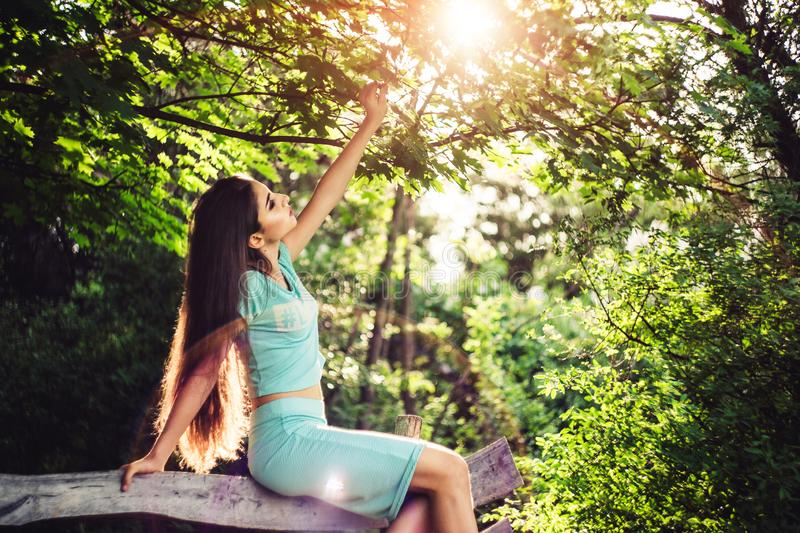 Wonderful spring. Beautiful young girl enjoys nature and sunlight sitting on a wooden bench in the park. royalty free stock images