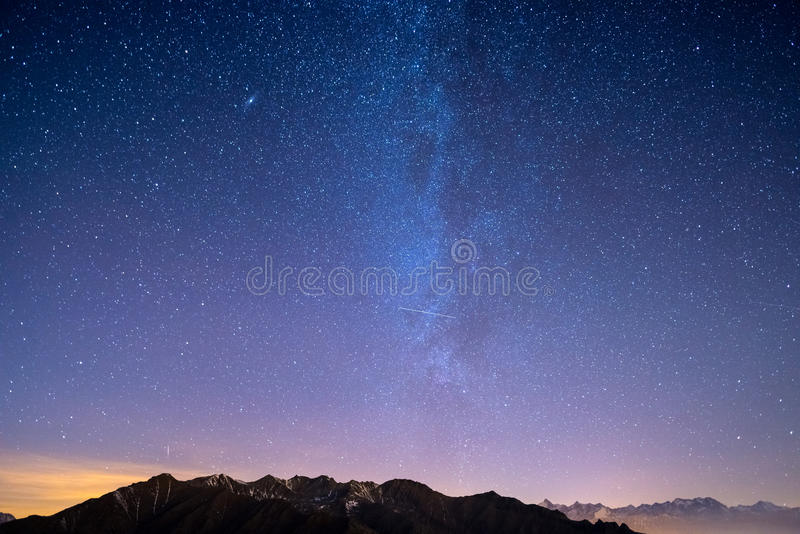 The wonderful starry sky on Christmas time and the majestic high mountain range of the Italian French Alps, with glowing villages. Below and moonlight royalty free stock photo