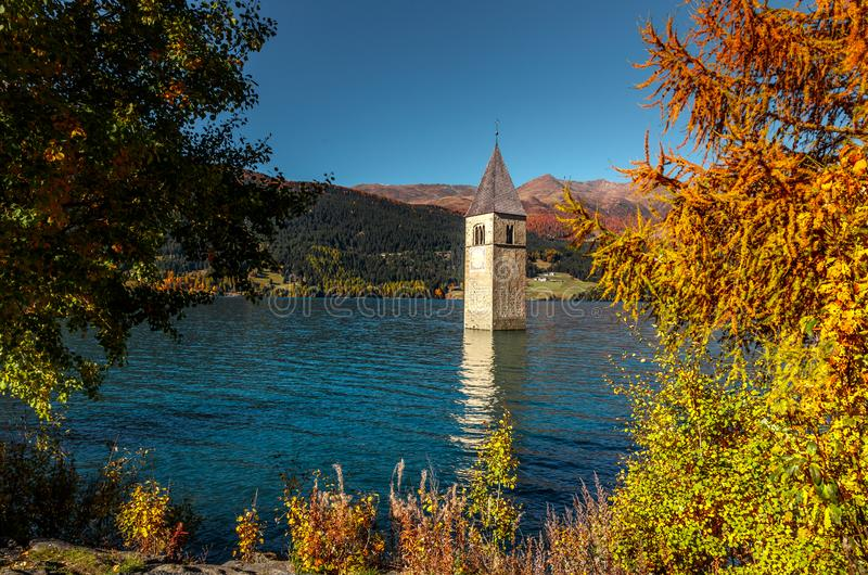 Wonderful Sunny Landscape. Amazing view of the lake Resia. perfect blue sky over the azure water in lake. Bell tower of the stock images