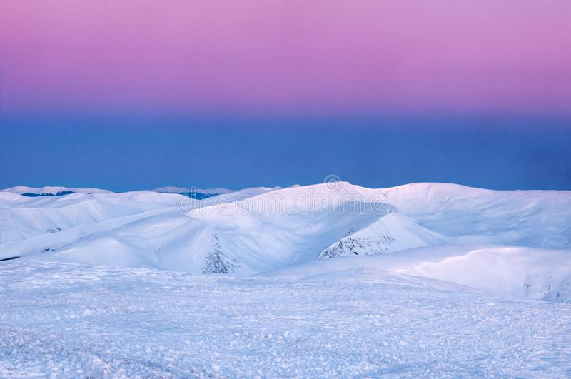Wonderful sunrise in the Carpathians in winter. Snow-covered summits of winter mountains in the red rays of sunrise. royalty free stock photography