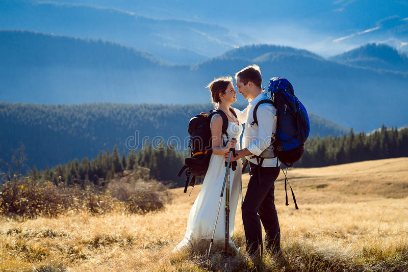 Wonderful tourist wedding couple kissing on the mountain peak stock image