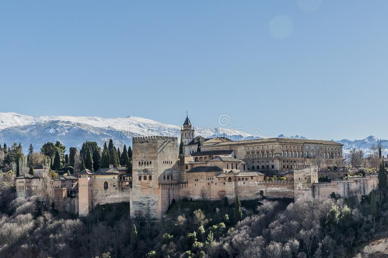 Wonderful view of the Alhambra on a hill with some green trees with a snowy mountain in the background. A beautiful sunny day with a blue sky in Granada Spain royalty free stock photo