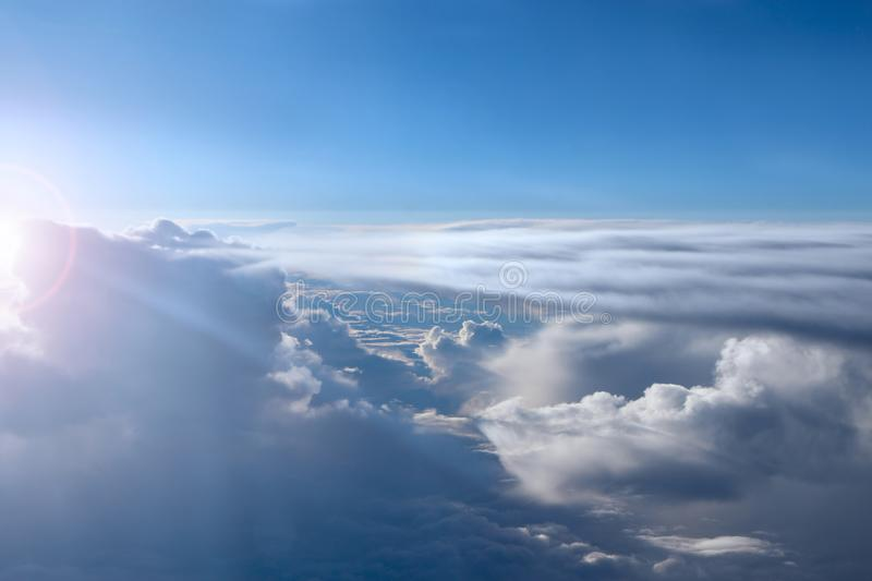 Wonderful view from window of plane in morning sun over clouds. Unusual clouds illuminated by rays of sun. Beautiful white clouds stock photos