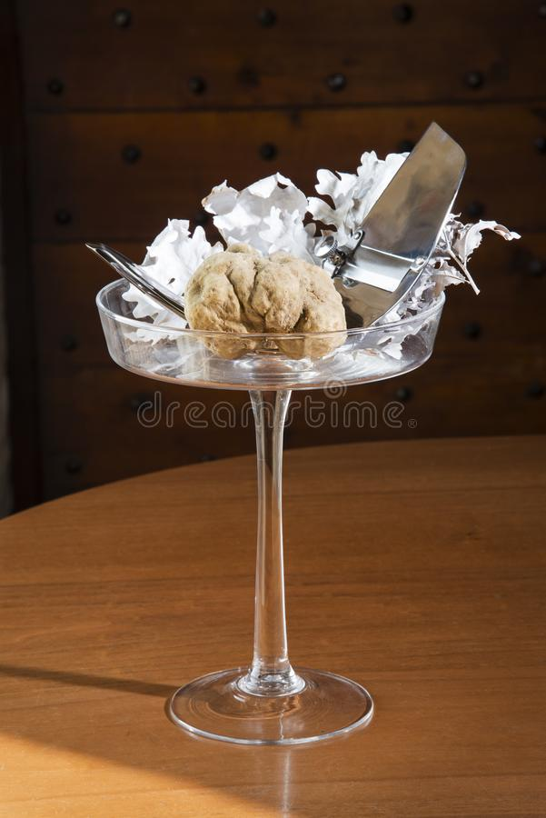 Wonderful white truffle on a glass cup with pedestal, with truffles cut in silver steel. On wooden table, from Langhe Alba in Piedmont Italy stock images