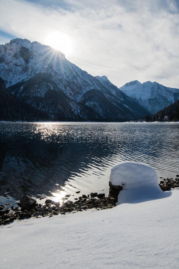Wonderful winter scenery on mountain pass lake lago del predil in snowfall and sunny weather, julian alps, italy. Wonderful winter scenery on mountain pass lake royalty free stock images