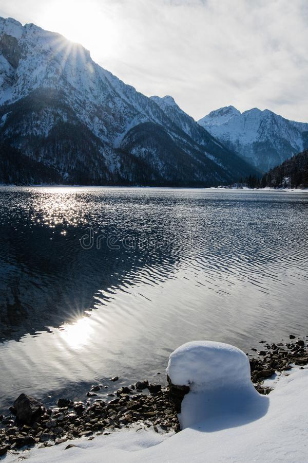 Wonderful winter scenery on mountain pass lake lago del predil in snowfall and sunny weather, julian alps, italy. Wonderful winter scenery on mountain pass lake stock photography