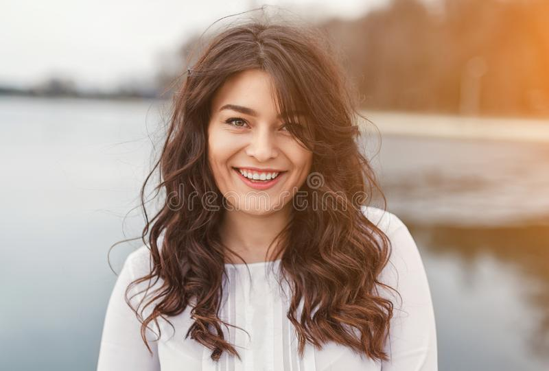 Wonderful young woman smiling at camera in nature royalty free stock photography