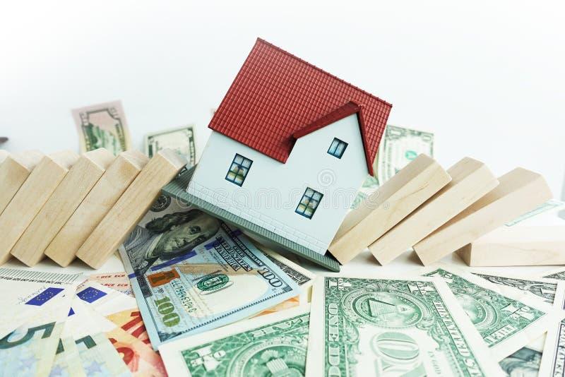 Woningmarkt die concept met miniatuur plastic huisdaling met dominostukken op contant geldbankbiljetten gaan verpletteren stock afbeelding