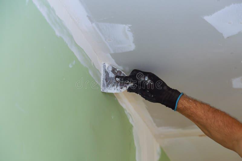 woningverbeteringen pleister op de muur met spatula stock afbeelding