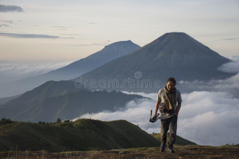 Climber enjoys the warm morning sun on the summit of Mount Prau royalty free stock photo