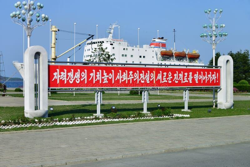 North Korea. Wonsan. Wonsan, North Korea - May 3, 2019: Propaganda banner and the Man Gyong Bong 92 cargo-passenger ferry moored at the pier and the promenade of royalty free stock photos