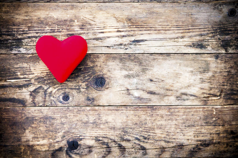 Wood background with red heart and nothing else. stock photography