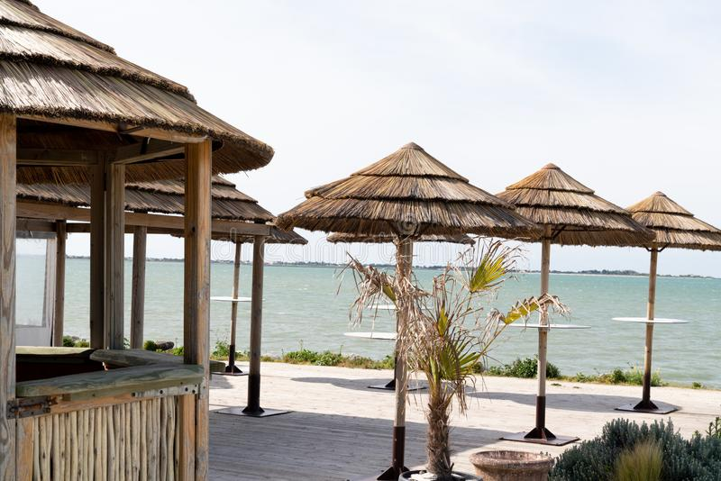 Wood bamboo hut as a bar straw roof on beach and many straw parasol in panoramic view. A wood bamboo hut as a bar straw roof on beach and many straw parasol in royalty free stock photography