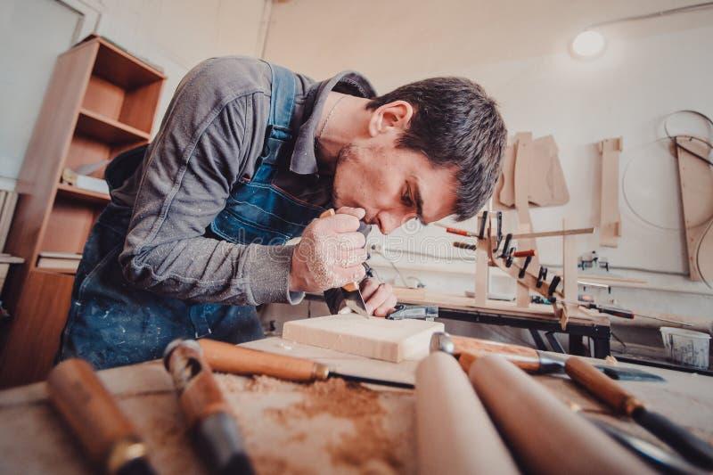 wood bearbeta Gammal träbakgrund Träskulptur Snickaren använder en bitande kniv för att inrama royaltyfria bilder