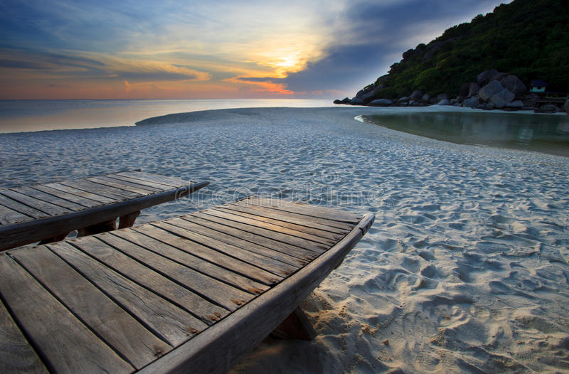 Wood bed on beach in dusky sky royalty free stock image