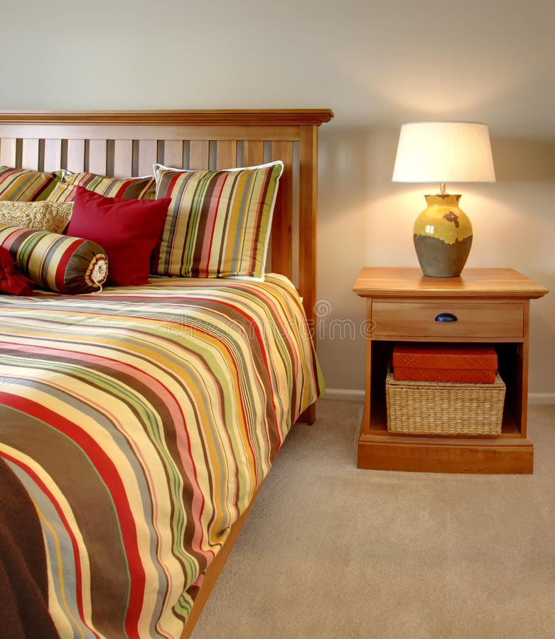 Wood bed and nightstand with stripes. In red, yellow and green with beige carpet royalty free stock photo