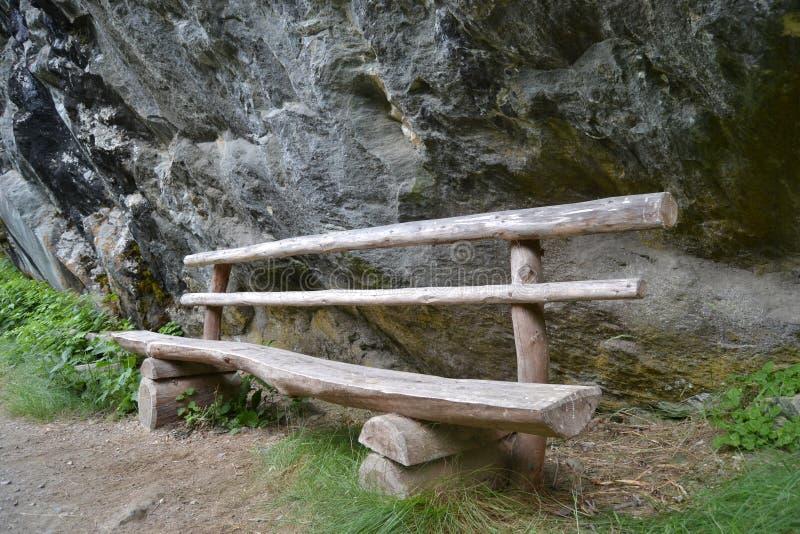 Wood bench along rocks stock photo
