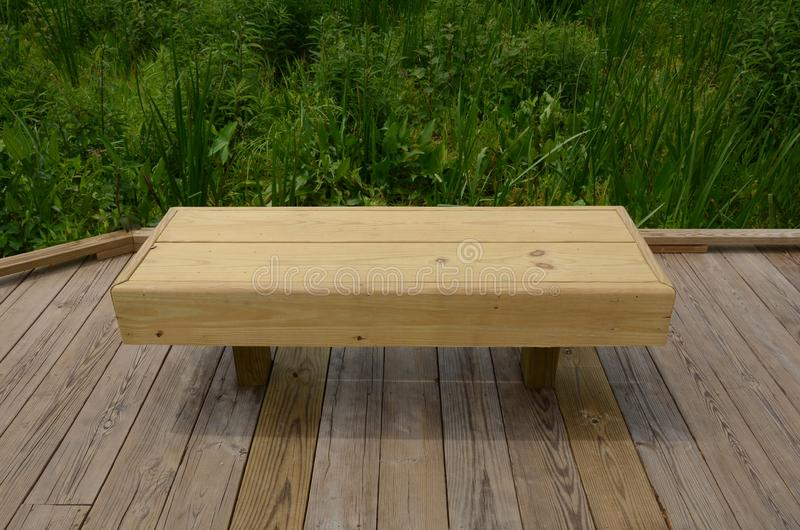 Wood bench or seat on boardwalk with green plants royalty free stock photography