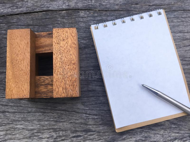 Wood block construction model put beside white notebook and sliver pen. Space on paper note book for write message royalty free stock photography