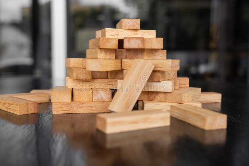 Wood block pile with architecture model with classic black tone background, Concept Risk management and strategy plan, growth. Business success process and team stock photography