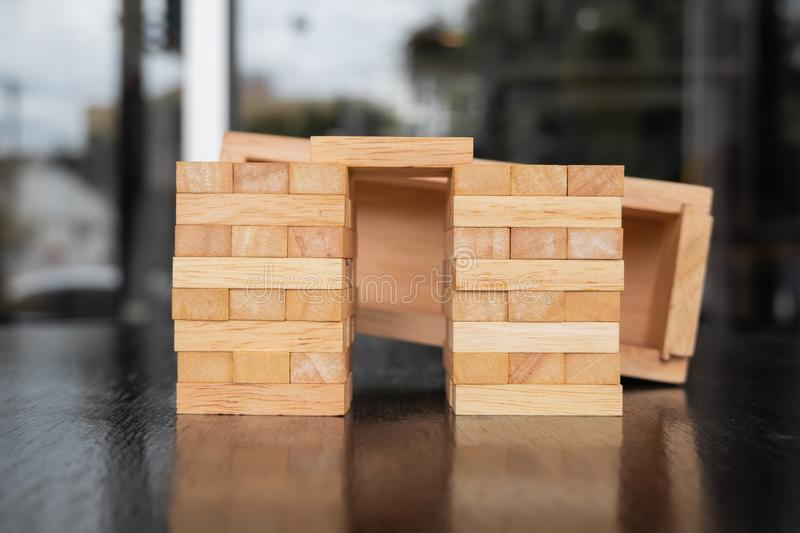 Wood block pile with architecture model with classic black tone background, Concept Risk management and strategy plan, growth. Business success process and team stock photo
