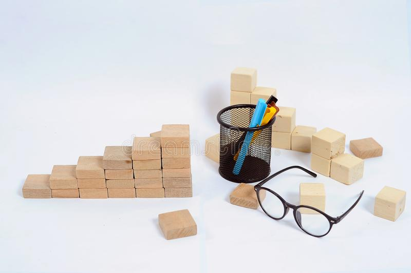 Wood block stacking as step stair on wooden table. Business concept for growth success process with color marker case and glasses royalty free stock images