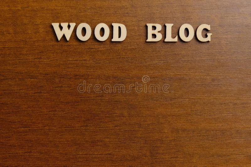 WOOD BLOG. An inscription made of wooden letters against the background of a dark brown wood. Copy space. stock photo