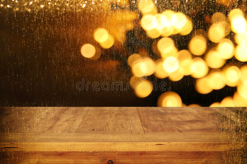 wood board table in front of Christmas warm gold garland lights on wooden rustic background royalty free stock photography