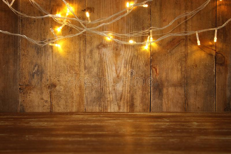 wood board table in front of Christmas warm gold garland lights on wooden rustic background. glitter overlay stock photo