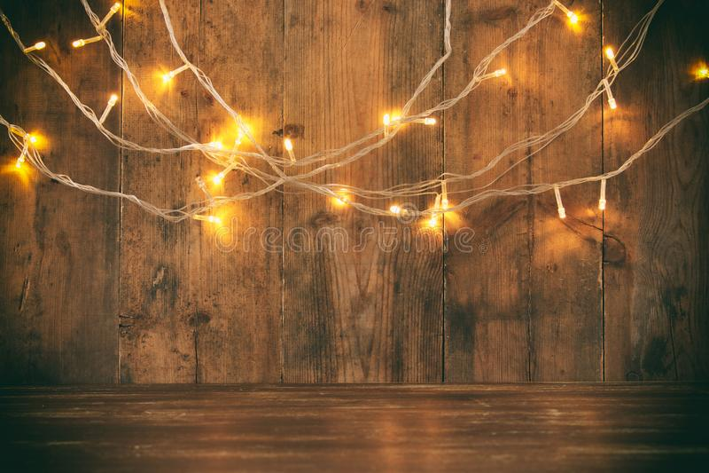 wood board table in front of Christmas warm gold garland lights on wooden rustic background. glitter overlay royalty free stock photo