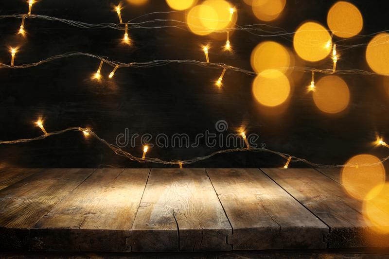 wood board table in front of Christmas warm gold garland lights on wooden rustic background. royalty free stock photo