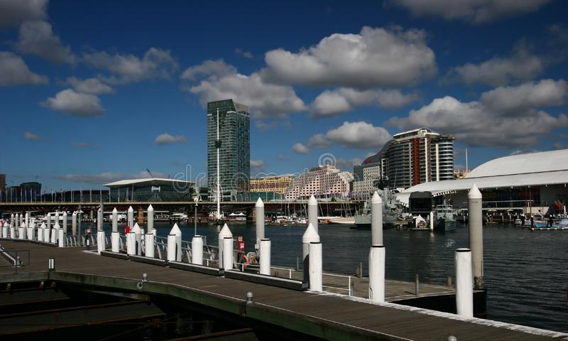 Wood boardwalk deck with mooring posts at city harbor waterfront with iconic cityscape in Cockle Bay, Darling Harbour, Sydney royalty free stock image