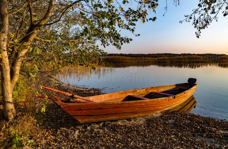 Wood boat on lake shore royalty free stock photography