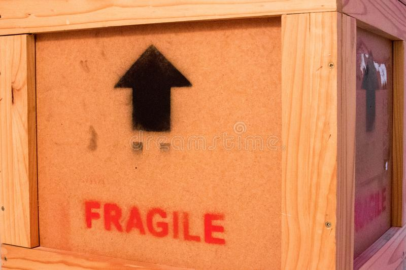 Wood box fragile red sign black arrow stock image