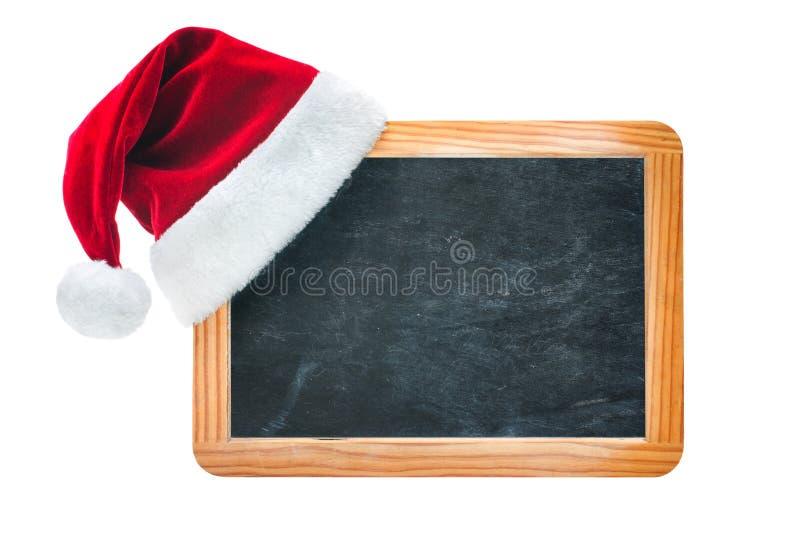 Wood bräde med jultomtenhatten royaltyfri foto