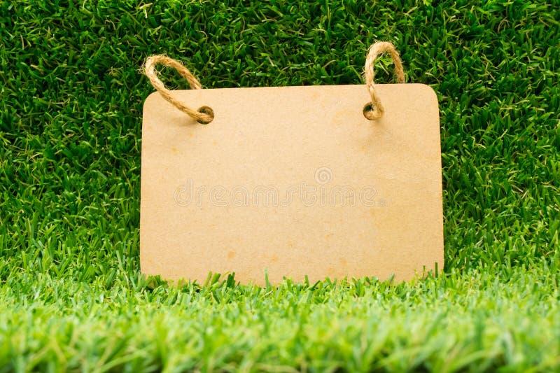 Wood bräde på gräset royaltyfria foton