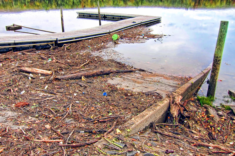 Wood Branch Debris and Trash after a River Flood. Wood tree branch debris and flooding trash pile accumulation against a floating launch dock after a river flood royalty free stock images