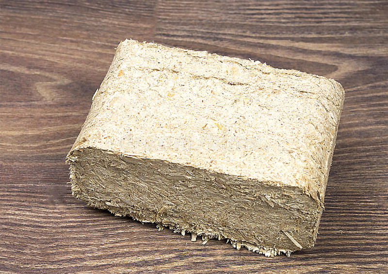 Wood briquette. Birch wooden briquette on brown background royalty free stock photos